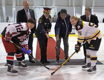 Team captains Zhang Mengying, left, and Emma Smith take part in a ceremonial puck drop with city councillor Gary Oosterhof, Kingston Police Deputy Chief Antje McNeely, Qiqihar Ice Hockey Association president Sun Huanwei and Original Hockey Hall of Fame vice-president Larry Paquette prior to the start of the Two Nations exhibition game at the Invista Centre in Kingston on Saturday, Sept. 23. The Kingston Ice Wolves defeated the Qiqihar Randy Women's Ice Hockey Club 3-2 in a shootout decision. (Steph Crosier/The Whig-Standard/Postmedia Network)