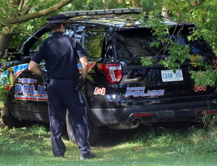 OPP Const. Jamie Stanley takes a look at a stolen police cruiser that crashed behind an apartment complex on Monday, Sept. 25, 2017 in Listowel, Ont. (Terry Bridge/Stratford Beacon Herald)