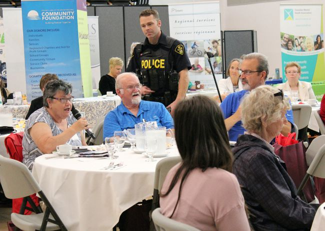 A participant at the Senior's Symposium poses a question to OPP Const. Ronni Grosenick (not pictured) during her presentation on how to avoid scams, held at the Seven Generations Education Institute on Friday, Sept. 22. More than 60 people attended the symposium.