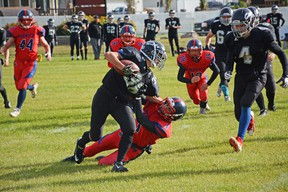 A Whitecourt Cats player gets tackled while running with a football on Sept. 22 (Peter Shokeir | Whitecourt Star).