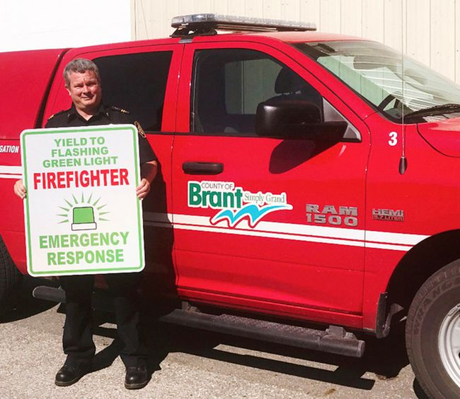 Brant fire prevention officer Jeff Balkwill holds a sign remind motorists to yield ot flashing green lights used by volunteer firefighters on their vehicles on the way to emergency calls. (Submitted Photo)