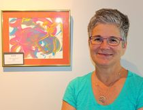 Marietta Drost, executive director of L'Arche London, stands in the new Gathering Place gallery, where a curated collection of brightly coloured art created by L'Arche participants hangs. (ANDREA COX, Special to Postmedia News)