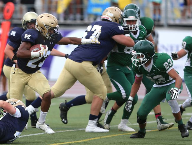 """Behind the massive blocking of 6'6"""" 270 pound offensive tackle Zack Fry, Otito Nwagou of RMC has lots of room to run against the MTS Spartans.The Titans won 37-14 after opening up a 28-0 lead in the first half of their United Way football game Wednesday September 27, 2017 at TD Stadium. Mike Hensen/The London Free Press/Postmedia Network"""