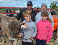 Percey Roney, 11, with Chocolate, the heifer he showed at the Sydenham Fall Fair Thursday. He's with his parents, Jim and Wilma, and his sister, Leeann, 9, who also showed a cow from the family's Owen Sound-area dairy farm. (Scott Dunn/The Sun Times)