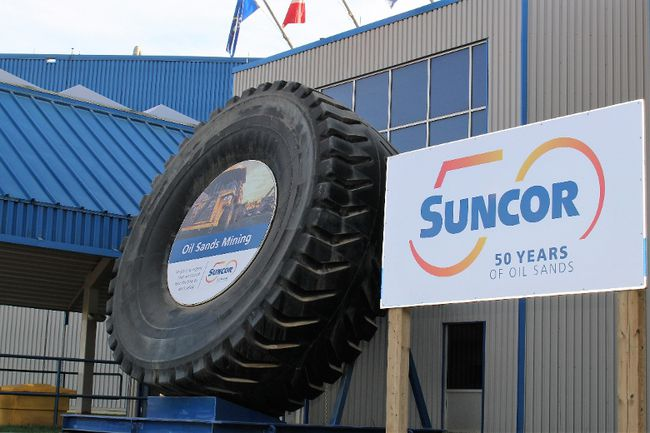"A sign celebrating Suncor Energy's 50th anniversary stands next to the ""big tire"" at its site north of Fort McMurray, Alta. on Wednesday September 27, 2017. Vincent McDermott/Fort McMurray Today/Postmedia Network"