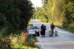 This file photo taken on August 20, 2017 shows a cab dropping off a couple of asylum seekers at the U.S./Canada border near Champlain, New York. (GEOFF ROBINS/Getty Images)