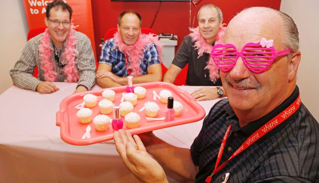 Luke Hendry/The Intelligencer Lou Lanthier, the Belleville and Ottawa site leader for Avaya Canada Corp., holds a tray of cupcakes, nail polish and pink ribbons at the company's Sidney Street office in Belleville Friday. Joining him were staff Chris McArthur, left, Scott LaTour and Bob Dafoe. Staff of the telecommunications company are preparing to raise funds for the Canadian Cancer Society's Breast Cancer Awareness Month through cupcake sales, pink manicures and more.