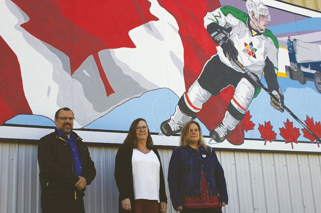 Local artists, from left to right, Mike Blume, Lee Beaton and Suzy Laevens stand in front of the mural the three painted at a public unveiling outside of the BDO Centre Friday morning. (Brian Oliver/The Graphic)