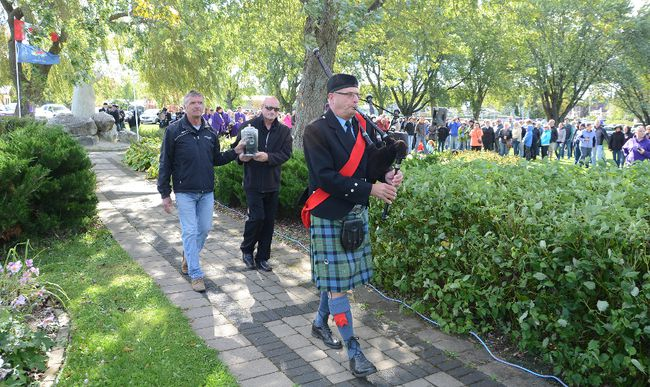 Don Crain, left, and Gord Glover carry an urn carrying Wiarton Willie's ashes led by piper Chris MacDougald after a ceremony at Bluewater Park in Wiarton on Saturday (Rob Gowan The Sun Times)