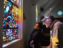 Nicky Alexander, left, and Peter Colbert examine the details in one of St. Matthew's Anglican Cathedral's stained glass windows on Saturday. The church was open for tours for Doors Open Timmins.