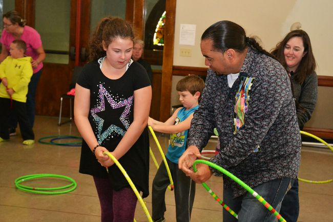 Former competitive hoop dancer, Adrian Harjo, helps Siearrah Davey with one of the moves he taught at his Hoop Dance Workshop Saturday afternoon.
