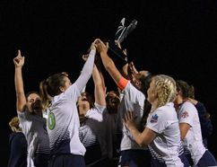 FC London women's team players celebrate with the trophy after clinching first place in League1 Ontario on Saturday in Mississauga, the team's second straight championship. (League1 Ontario/Martin Bazyl Photography)