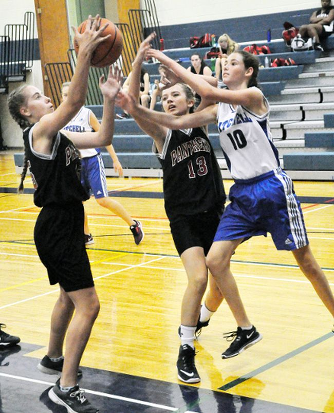 Haley Small (right), of the MDHS junior girls basketball team, reaches for a loose ball against visiting South Huron last Wednesday, Sept. 27.  ANDY BADER/MITCHELL ADVOCATE