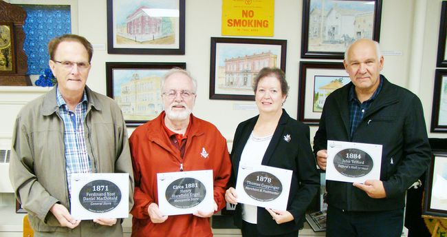 Building owners J.D. Lyons, left, and Lyle Schaus, right, along with Hanover Heritage Committee chair Al Morrow and Hanover mayor Sue Paterson, display prints of the historical building signs during an unveiling ceremony on Sept. 29. The signs are being made into plaques and will be placed on historical buildings in Hanover.