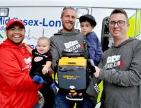 Sav Neth (left) and Logan Neth, Patrick Taylor and Jordan Neth, and Alex Davy hold an Automated Electronic Defibrillator at Middlesex-London EMS headquarters. Sav, Patrick, and Alex are members of Dad Club London, a local support group that recently gifted the Thames Valley District School Board with $50,000 to place AEDs in schools. (Chris Montanini\Londoner)