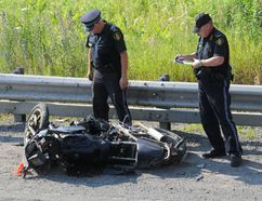 OPP officers look at a motorcycle on the side of Highway 401 following a fatal crash in this file photo.