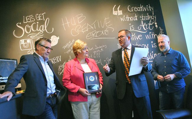 Coun. Darrin Canniff (centre right) proclaims HUB Creative Group as the Feature Industry for September. He's with owners Ike Erickson (left), Mary Genge and John Lyons at the Lacroix Street business.