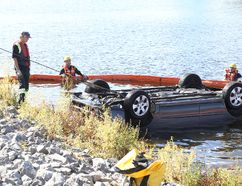 Jason Miller/The Intelligencer Firefighters cordon off an area around a car which ended up in the Moira River following a crash Wednesday evening. The vehicle was removed from the water early Thursday.