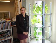Pembroke Public Library children's librarian Lioutsia Schizkoske posing next to the library's new Tower Garden which was funded by a grant from the County of Renfrew's Healthy Kids Community Challenge.