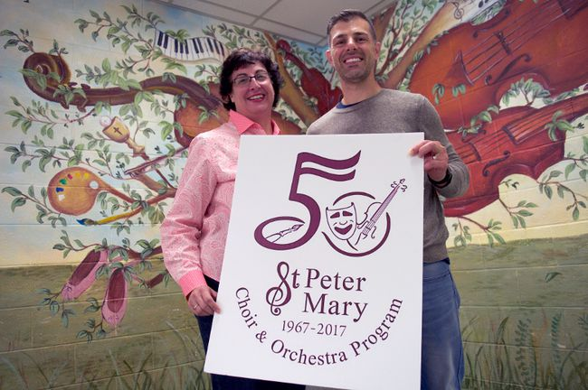 St. Mary choir school principal Lisa Gardi (left) and Grade 8 teacher Steve Chiras, hold a poster for the Catholic elementary school's upcoming 50th anniversary celebrations. (Chris Montanini\Londoner)