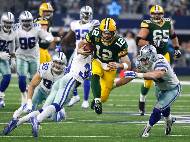 In this Jan. 15, 2017, file photo, Green Bay Packers quarterback Aaron Rodgers rushes for a gain as Dallas Cowboys' Sean Lee and Anthony Brown defend during NFL divisional playoff game in Arlington, Texas. (AP Photo/Michael Ainsworth, File)