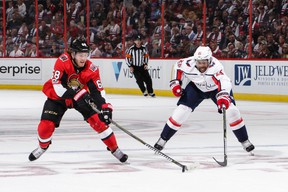 Ottawa's Mike Hoffman (left) skates with the puck against the Caps' Devante Smith-Pelly during the Sens' season opener at Canadian Tire Centre last night. (Getty Images)