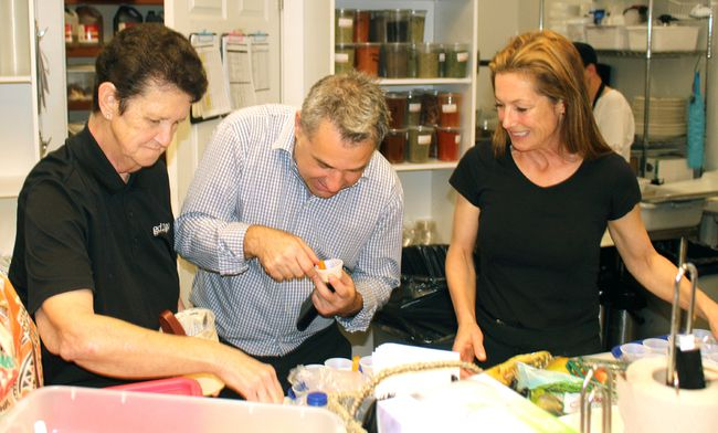 Jackie Bishop, left, and Tracey Vigars watch as Ben Farella samples some carrots and tahini dip, Thursday, at the official opening of Gd2go on MacIntyre Street West. The business has been operating at its new location for the past couple of months. It moved from the Main Street East location it had occupied since opening in 2013. 