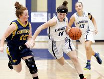 Ursuline Lancers' Reece Cowan, right, is defended by CKSS Golden Hawks' Mary Turner in the first half of an LKSSAA 'AA-AAA' senior girls' basketball game at Ursuline College Chatham on Thursday, Oct. 5, 2017. (MARK MALONE/The Daily News)