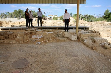 In this Tuesday, Sept. 26, 2017 photo, Junaid Sorosh-Wali, right, a UNESCO official, inspects the remains of a mosaic at St. Hilarion monastery, a site of early Christianity, in Nusseirat, central Gaza Strip. (AP Photo/Adel Hana)