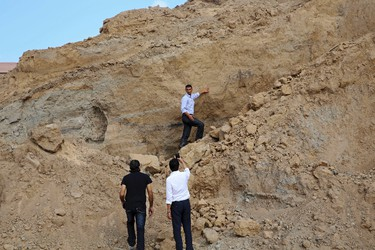 In this Tuesday, Sept. 26, 2017 photo, Junaid Sorosh-Wali, a UNESCO official, takes photos while Fadel al-A'utul, a worker with French excavation mission, explains to him the damage at Tel Es-Sakan hill, south of Gaza City. (AP Photo/Adel Hana)