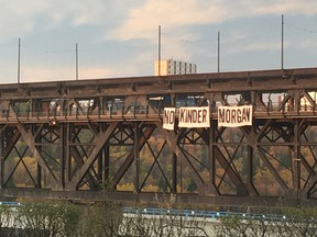 Activists dropped a 50-foot-wide banner from the High Level Bridge in Edmonton Friday morning to protest a proposed pipeline expansion through British Columbia.