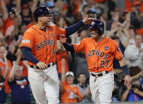 Astros' George Springer (left) and Jose Altuve (right) celebrate after they scored on teammate Carlos Correa's double in Game 2 of the American League Division Series against the Red Sox in Houston on Friday, Oct. 6, 2017. (David J. Phillip/AP Photo)
