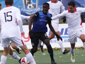 FC Edmonton midfielder Abraham Dukuly, centre, dribbles the ball between three members of the San Francisco Deltas in North American Soccer League play at Clarke Stadium on Sunday, Oct. 1, 2017.