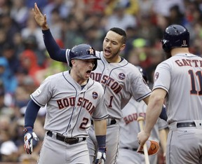 Astros third baseman Alex Bregman (2) celebrates his home run with Carlos Correa (rear) and Evan Gattis (right) during the eighth inning of Game 4 of the American League Division Series against the Red Sox in Boston on Monday, Oct. 9, 2017. (Charles Krupa/AP Photo)