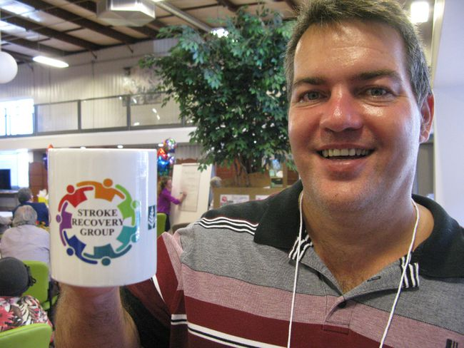 Raymond Knight displays a coffee cup bearing the new logo of the Stroke Recovery Group at the Adult Recreation Therapy Centre. Knight, a stroke survivor, created the logo,  which was on display at an open house on Tuesday. (VINCENT BALL/The Expositor)