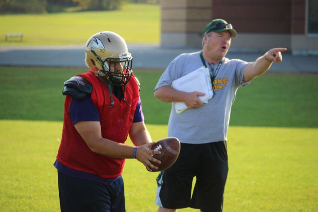 Falcons head coach Jeff McAllister makes his point while quarterback Tyler Fisher makes a throw at a Tuesday afternoon workout at Holy Trinity. Todd Hambleton/Cornwall Standard-Freeholder