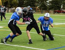 Matayo Redbear of the Lacombe Bantam Raiders is hauled down by two Hunting Hills Lightning opponents at MEGlobal Athletic Park on Saturday afternoon. The Raiders lost 24-0 to the Lightning. (Ashli Barrett/Lacombe Globe)