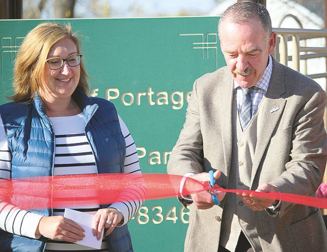 Portage Mayor Irvine Ferris cuts the ribbon at Tuesday unveiling of Central Park as Community Foundation of Portage and District chair Carey Duncan looks on. (Brian Oliver/The Graphic)
