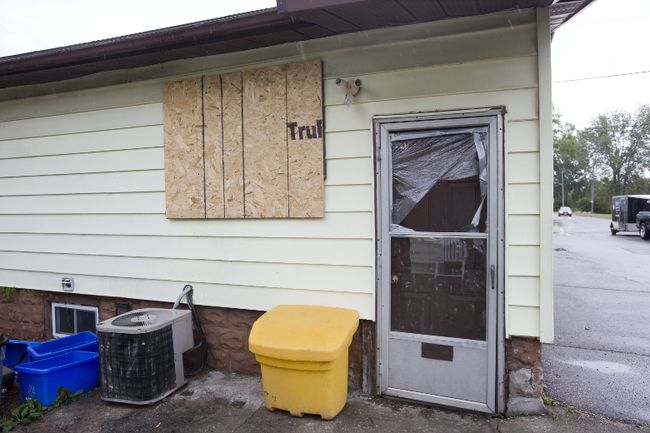 Windows are boarded up and broken at  the London house where Raymond Beaver was stabbed to death during a home invasion last week. (DEREK RUTTAN, The London Free Press)