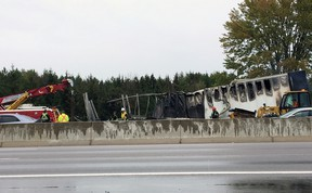 Tow truck operations remove the burnt carcass of a transport truck on Highway 401 in Kingston, Ont. on Wednesday October 11, 2017. Steph Crosier/Kingston Whig-Standard/Postmedia Network