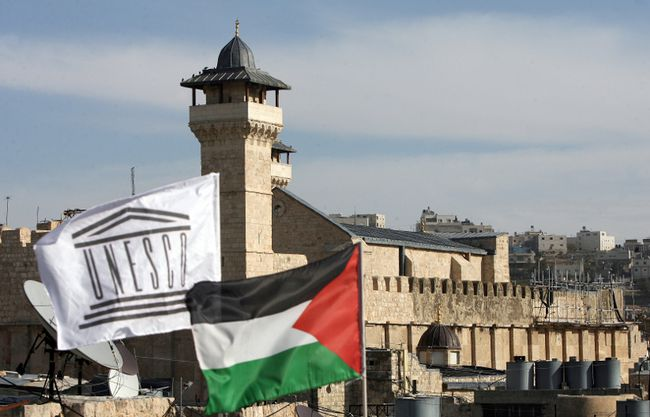 The UNESCO flag flies next to the national Palestinian flag in front of Hebron's Ibrahimi Mosque or the Tomb of the Patriarchs in the southern West Bank city's old quarter on December 13, 2011. (Hazem Bader/Getty Images)