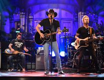 """In this photo provided by NBC, Jason Aldean performs """"I Won't Back Down"""" on """"Saturday Night Live,"""" in New York on Oct. 7, 2017. Aldean will return to touring following the Las Vegas mass shooting on Oct. 1. (Will Heath/NBC via AP)"""