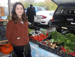 Mel Green of Green Masks stands next to a vegetable vendor's wares at the Pembroke Farmer's Market. She has started the Everybody Eats program, which collects and sells fresh food at a fraction of the cost so people who normally wouldn't be able to afford it can have access to nutritious food.