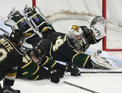 Jason Kryk/postmedia news London Knights goalie Tyler Johnson and teammates dive to deny a Spitfires chance during the first period of their OHL game at the WFCU Centre in Windsor on Thursday night. The Spitfires scored twice late to win 3-1.