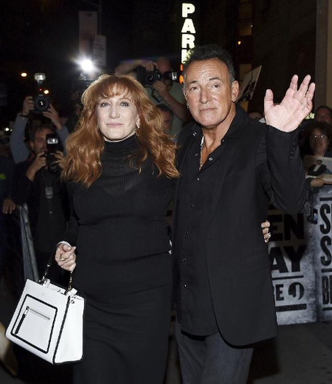 """Bruce Springsteen and his wife Patti Scialfa exit out the stage door after the """"Springsteen On Broadway"""" opening night performance at the Walter Kerr Theatre in New York on Thursday, Oct. 12, 2017. (Evan Agostini/Invision/AP)"""