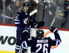 Winnipeg Jets' Nikolaj Ehlers (27) and Blake Wheeler (26) celebrate after Ehlers' goal during third period NHL hockey action against the Carolina Hurricanes, in Winnipeg, Saturday, October 14, 2017. THE CANADIAN PRESS/Trevor Hagan
