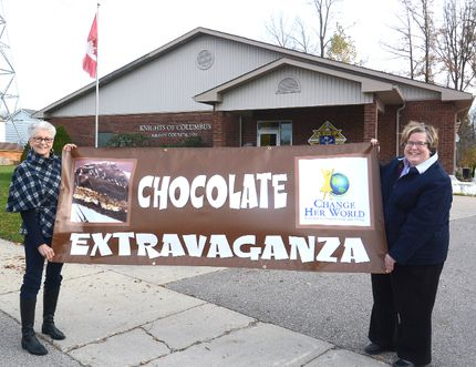 Change Her World co-founders Linda Willis and Carol Hamilton hold a Chocolate Extravaganza poster in front of the Knights of Columbus hall in this Beacon Herald file photo. The event returns Nov. 4 from 10 a.m. to 2 p.m. Scott Wishart/Stratford Beacon Herald/Postmedia Network File Photo