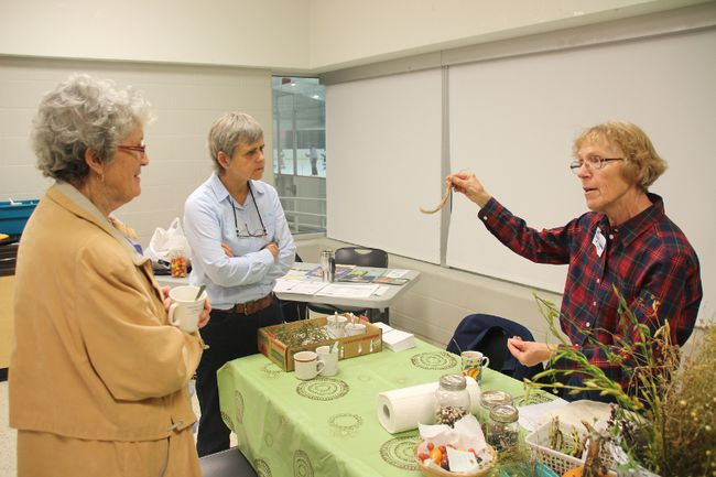 Anke Craig holds up a bean pod during her seed preservation demonstration.