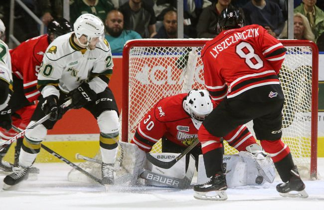 Knights Adrian Carbonara tries to get his stick free to jam a puck past Owen Sound goaltender Zack Bowman during their game at Budweiser Gardens on Sunday October 15, 2017. Alan Lyszczarczyk of the Attack is coming back to help. (MIKE HENSEN, The London Free Press)