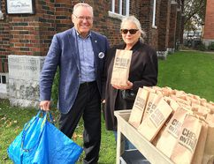 Denis Doyle and Tara Kainer, at Princess Street United Church in Kingston, were among the many volunteers handing out lunch bags on Tuesday promoting the Chew On This! campaign on International Day for the Eradication of Poverty. (Mike Norris/The Whig-Standard)